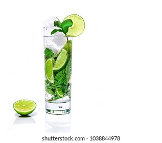 A tall glass with mojito, ice, mint and lime stands on a white background in the studio.Food, drinks, ice, mint, lime, glass, white background.
