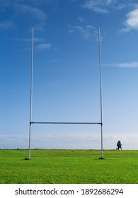 Tall goal post for Irish National sport rugby, hurling, gaelic football and camogie on a green training pitch, blue cloudy sky. Couple walking in the background