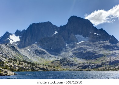 Tall granite peak rises over a blue alpine lake in the high sierra