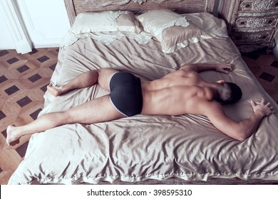 Tall guy in black underpants lies full body on grand bed back to camera
