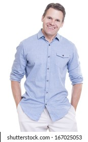 Tall handsome Caucasian man stands on white background with hands in pocket and big smile