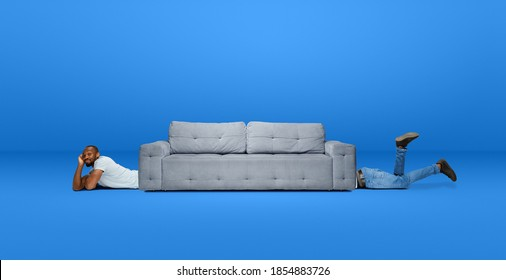 Tall high man and long sofa isolated on blue studio background. Unusual delighted and long. Copyspace for offer, advertising, artwork, inspiration and hobby, mood concept. Humor, weird collage.