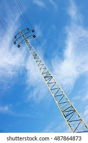 Tall high voltage tower (electricity post), blue sky with white clouds.