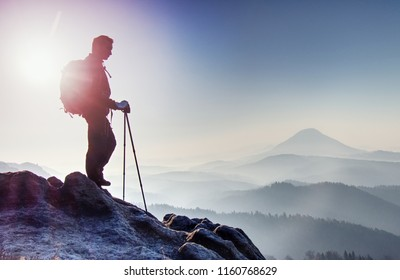 Tall hiker with backpack and trekking poles walk mountain trail. Rocky part of path with view into distance. Hilly landscape bellow.