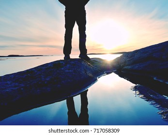 Tall hiker in dark sportswear with sporty backpack stands on cliff above sea. Man enjoy amazing sunset at horizon with pink orange sky with clouds. Magic autumn day on offshore.