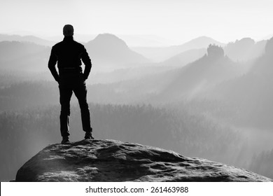 Tall hiker stand on peak of sandstone rock in rock empires park and watching over misty and foggy morning valley to Sun. Beautiful moment miracle of nature.Men silhouette stand.Tall shadow.Cold sunset