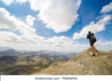 Tall hiker stand on peak of sandstone rock and watching over cloudy amazing landscape to Sun. Beautiful moment miracle of nature blue sky seen from the peak of the mountains