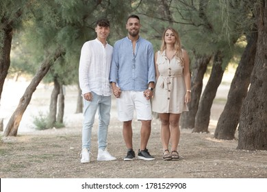 A tall Italian man with a beard a blonde Italian woman with long hair and an Italian boy with short hair together in a park with trees and very blurred background
