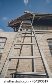 Tall ladder at an old building with damaged roof