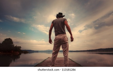 tall man in a cowboy hat standing on the jetty and waiting for the storm that is coming, dark dark sky