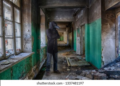Tall man in leather plague doctor  mask and mantle with hood inside abandoned building. Monster or ghost for horror