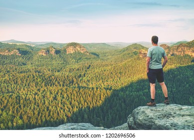 Tall man in outdoor clothes stands alone on the peak of rock. Hiker watching hilly forest landsape in morning mist.