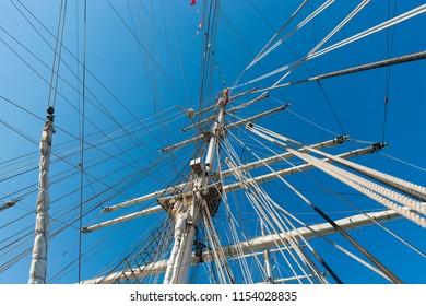 Tall mast of a sailing ship on the sunny blue sky