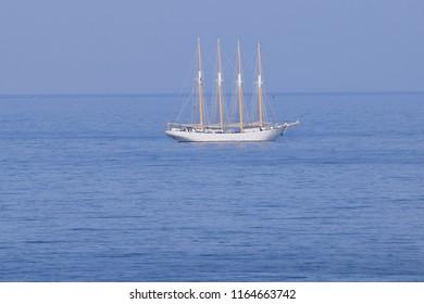 A tall masted ship, anchored alone