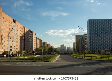 Tall modern buildings along the street in the city of Mytishchi. The street goes away. Cars are driving on the road. Moscow region, Russia.