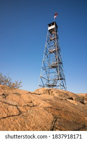 A tall mountain fire tower sitting on a rocky summit. Beacon, New York