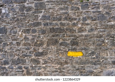 Tall old gray stone wall with one stone highlighted painted bright yellow