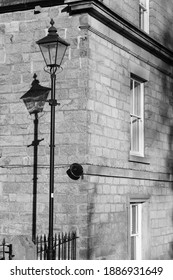 Tall old style black lamp post casting a shadow on a stone wall of a house.