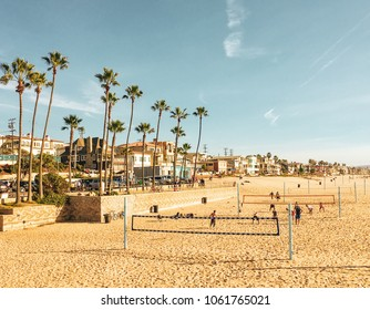 Tall palm trees, parking lot, beachfront homes on the Strand, and people playing beach volleyball in Manhattan Beach, Los Angeles, California. Travel, urban living, active lifestyle and sports concept