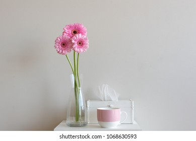 Tall pink gerberas in glass with tissue box and pink mug on small white table against neutral wall background