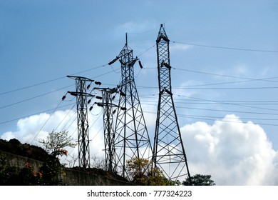 Tall pylons carrying high tension power cables in a drive to carry electricity and power to even remotest parts of India isolated against blue sky