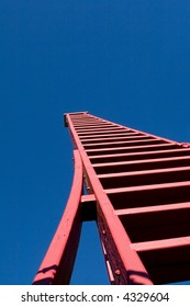 Tall red wooden ladder viewed from low angle.