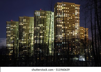 Tall residential buildings and silhouettes of trees in park at night
