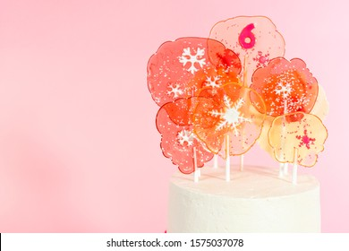Tall round cake with Italian buttercream frosting decorated with fondant snowflakes and topped with large pink and white lollipops on pink background.