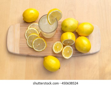 A tall round glass of Lime Juice with lime sliced on a wooden chopping board.