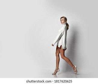 Tall sexy slim long-legged blonde woman in knitted sweater on a naked body and high-heeled shoes walks relaxed towards copy space. Side view. Sexy female look and perfect body concept