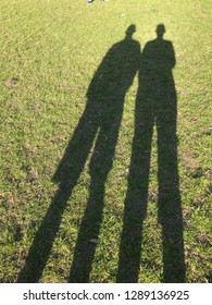 Tall shadows of two people outside on a sunny day.