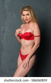 Tall shapely blonde woman dressed in red lingerie