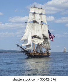 A tall ship known as a brigantine sails on blue water with an American flag flying