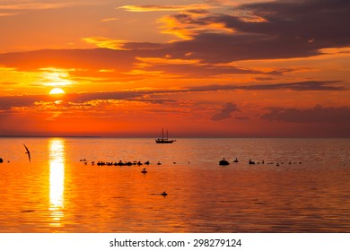 tall ship sailing along skyline during sunset