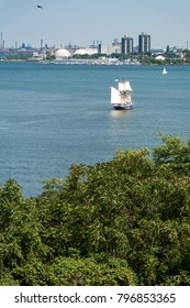 A tall ship sailing into the Hamilton harbour with industry in the background.