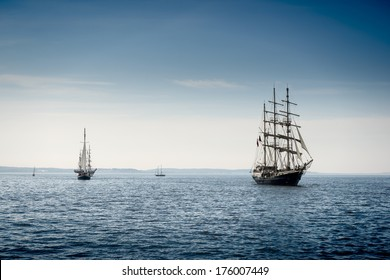 Tall ship sailing on blue water.