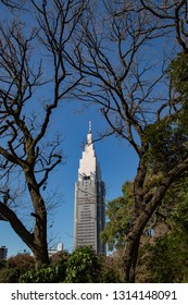 A tall skycrapper in the city of Tokyo with foreground of trees in Shinjuku park with no leaves during the early Spring.