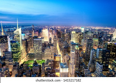 Tall skyscrapers of Midtown Manhattan, night aerial view.