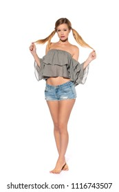 Tall slender blonde in a gray off the shoulder blouse and denim shorts