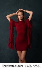 Tall slender blonde in a short red dress with voluminous sleeves