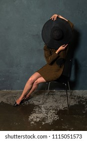 Tall slender Ukrainian brunette in a brown dress and black hat