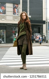 Tall slim girl crosses the road at a crosswalk. She is dressed in a boho style: brown coat, yellow bag, green sweater, shorts and torn stockings