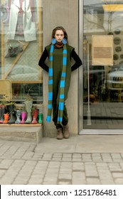 Tall slim girl standing at the wall of a vintage clothing store. She is dressed in a boho style: a green jumpsuit and a long blue scarf.