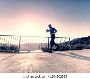 Tall slim man run on the lake terrace against the backdrop of a beautiful sunrise. Shore of mountain lake with dark forest hills