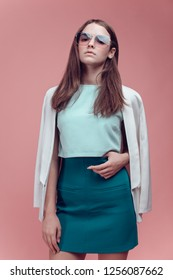 tall and slim model of European appearance posing at the camera of a photographer in a studio on a pink background for advertising. strict suit and green top. photo studio, ukraine.