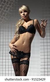 Tall slim sexy blonde model posing in black lingerie and suspenders studio shot facing camera