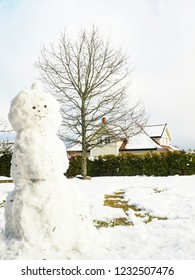 Tall snowman in front yard, to the left of tree, hedge and house in background