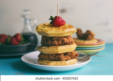 Tall stack of chicken and waffles shown with syrup and strawberries for garnish.