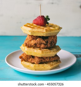 Tall stack of chicken and waffles with strawberry garnish.