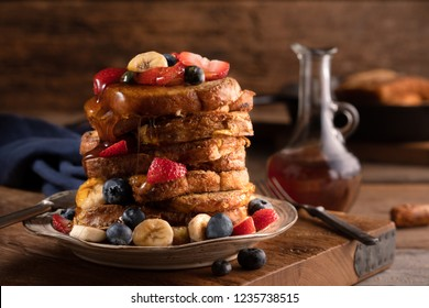 Tall stack of French toast covered with blueberries, strawberries, bananas and maple syrup in a rustic restaurant with a profile view in a horizonal format.